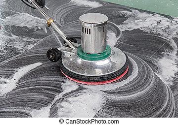 Thai people cleaning black granite floor with machine and...