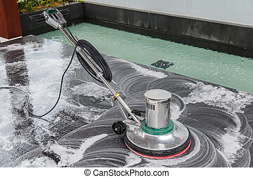 Thai people cleaning black granite floor with machine and chemic