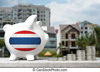 Thai real estate investment concept with piggy bank, stacks of coins and house in the background