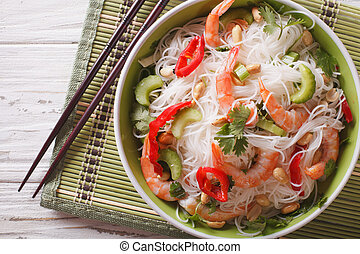 Thai salad with glass noodles, prawns and peanuts close-up. horizontal top view