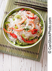 Thai salad with glass noodles, prawns and peanuts close-up. vertical top view