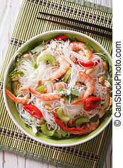 Thai salad with glass noodles, prawns and vegetables macro. vertical top view