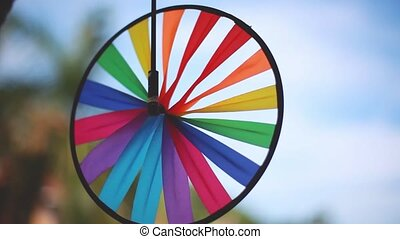 Thai street decoration. Close up of colorful spinner on blurred blue sky background.