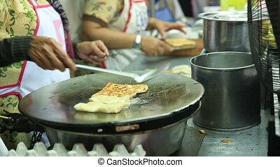 Thai street vendor fries up delicious roti in chiangmai, thailand