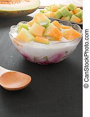 Thai style sweet dessert, muskmelon eat with sweet coconut milk on black background