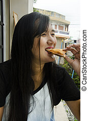 Thai woman eating hot sandwiches tuna at coffee shop