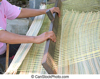 Thai woman hands weaving reed mat