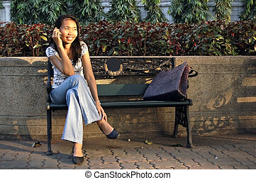Thai woman on a park bench making a phonecall