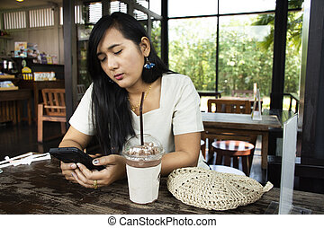 Thai woman sitting relaxed playing smartphone and drinking frappe chocolate in coffee shop