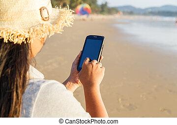 Thai Woman using smartphone at the beach