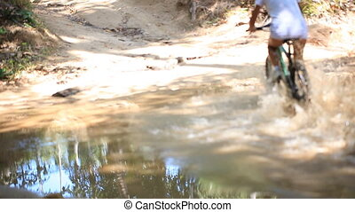 THAILAND, KOH SAMUI, OCTOBER 2, 2013: cyclists rides through the jungle in a puddle on sunny day. Video