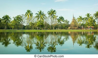 Thailand, Sukhothai - a park with a pond and palm trees on the shore