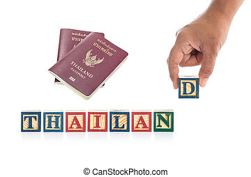 """THAILAND"" write in colorful wood alphabet blocks and hand holding ""D"" with Thailand passport isolated on white"