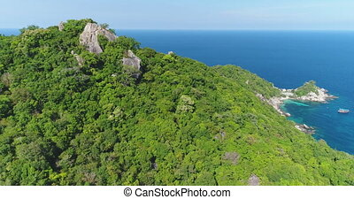 Thailand's mountain peaks aerial: green rainforest on hills with high leafy trees. Majestic seascape from top of mount. Beauty of Thai nature landscape of Koh Tao island. Cinematic shot in 4K, UHD
