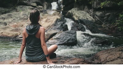 Thailand's river waterfall: woman rest on stones. Calm water flow on stream rock bottom. Girl relax