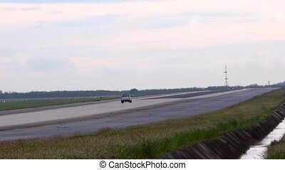 Thailland. Phuket International Airport. Airfield. The safety car coming down the runway. Slow Motion.