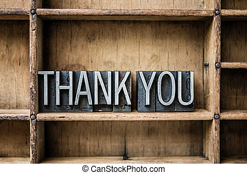 """The words """"THANK YOU"""" written in vintage metal letterpress type sitting in a wooden drawer."""