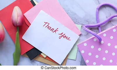 thank you message on sticky note with tulip flower on tiles background .