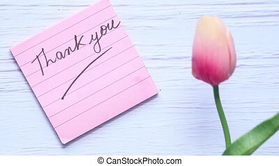 thank you message on sticky note with tulip flower on white background .