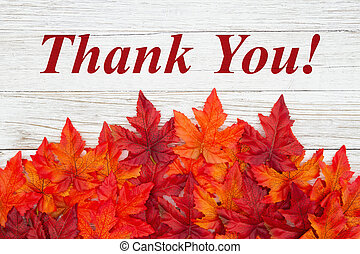 Thank you message with red and orange fall leaves on weathered wood