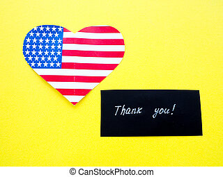 Thank you sign on a chalkboard with American flag on yellow background, USA