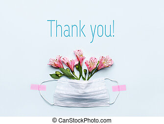 Thank You text with medical mask and pink flowers on blue background. Nurse day or Thanks to doctors concept