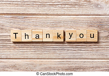 thank you word written on wood block. thank you text on table, concept