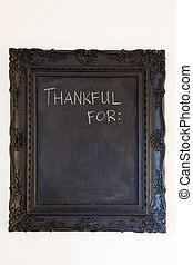 A black chalkboard on a white wall has the words thankful for: written on it along with the texture and interesting background of the chalkboard itself.