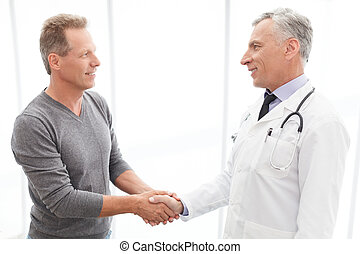 Thankful patient. Thankful mature patient shaking doctors hand