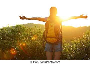 thankful woman hiker open arms to the sunrise stand at ...