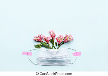 Thanks to Doctor and Nurses concept with medical mask and pink flowers on blue background with copy space