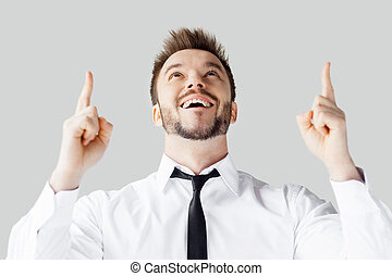Thanks to God! Handsome young man in shirt and tie pointing up and smiling while standing against grey background