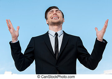 Thanks to God! Handsome young man in suit rising hands up and smiling while standing against blue sky