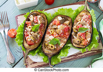 Thanksgiving Autumn Menu. Baked Stuffed Eggplant with Olives, Feta Cheese and Vegetables on a Rustic Table.