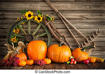 Thanksgiving autumnal still life with pumpkins and old wooden wheel