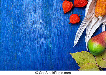 Thanksgiving background with autumn fruits and gourds on a blue rustic wooden table. Autumn harvest. Top view. Copy space. Thanksgiving frame