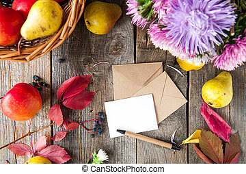 Thanksgiving background with seasonal fruits, flowers, greeting card and envelope on a rustic wooden table. Autumn harvest concept. Confession in feelings. Selective focus, Top view. Space for text.