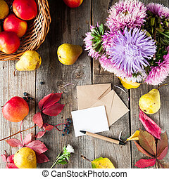 Thanksgiving background with seasonal fruits, flowers, greeting card, few craft envelopes on a rustic wooden table. Autumn harvest. Confession in feelings. Selective focus, Top view. Space for text.