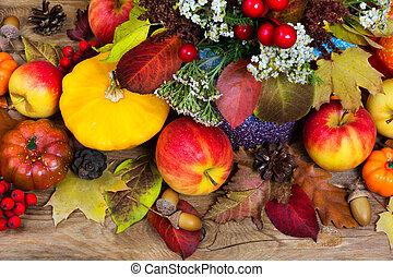 Thanksgiving background with yellow squash, apples, acorns, colorful fall leaves