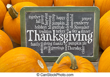 cloud of words related to celebration of Thanksgiving Day on a slate blackboard surrounded by pumpkins