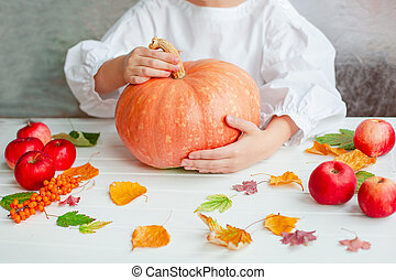 Thanksgiving concept. Hands holding pumpkin and apples, flowers, autumn leaves on a rustic table, flat lay.