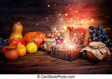 thanksgiving concept of pumpkins, apple, garlic, straw and opened chest treasure with mystical miracle light on wooden table, beautiful fine art design