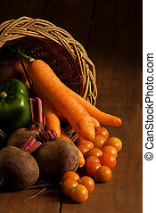 Thanksgiving cornucopia filled with autumn fruits and vegetables on wooden table.