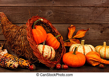Thanksgiving cornucopia with pumpkins against rustic wood