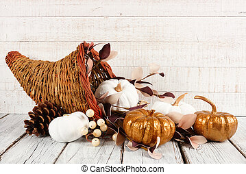 Thanksgiving cornucopia with white and gold pumpkins against white wood