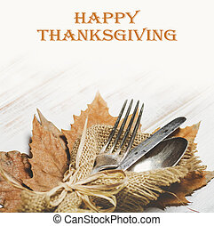 Thanksgiving dinner table setting with autumn leaves and...
