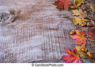 Thanksgiving greeting with acorn and fall leaves on wooden background