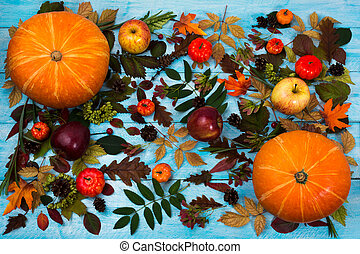Thanksgiving greeting with fall leaves and pumpkin on blue background