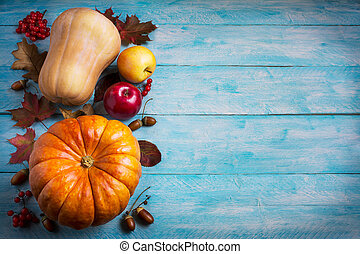 Thanksgiving greeting with orange pumpkins and fall leaves on blue background