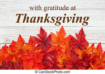 Thanksgiving greeting with red and orange fall leaves on weathered wood